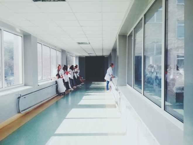 woman in white shirt standing near glass window inside room