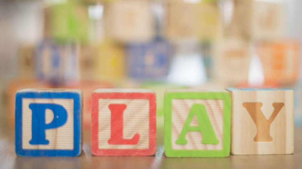 depth of field photography of p l a y wooden letter decors on top of beige wooden surface